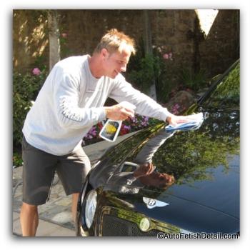 waxing black car in sun